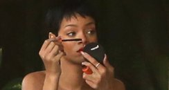 Rihanna wearing stripey dress applying make up
