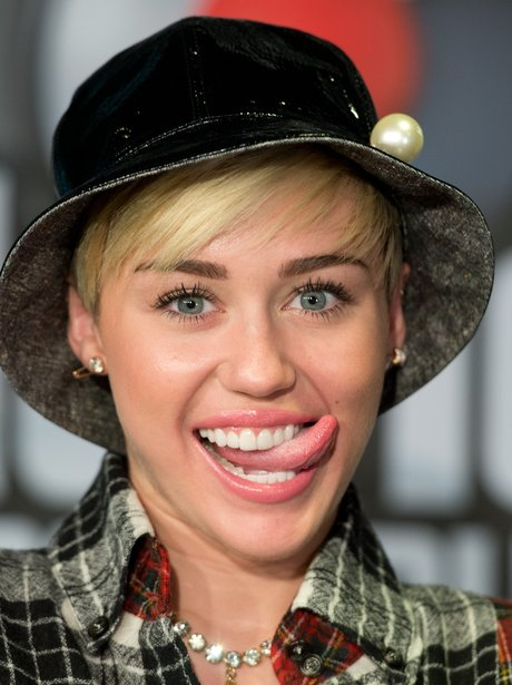 Miley Cyrus sticking tongue out in a hat